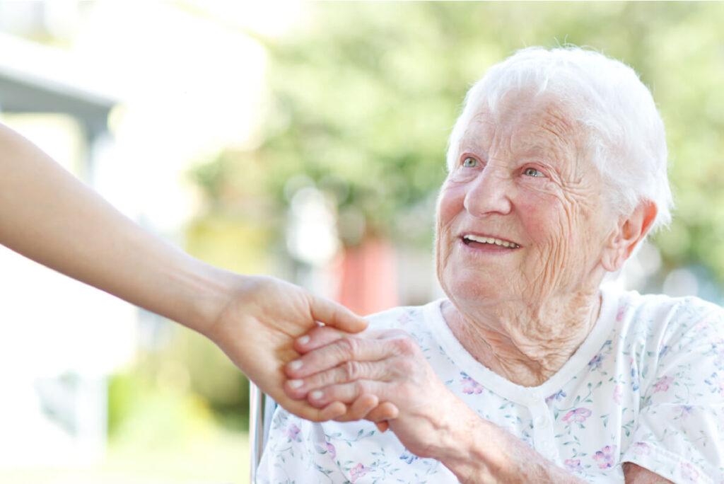 happy elderly mom holding her daughter's hand